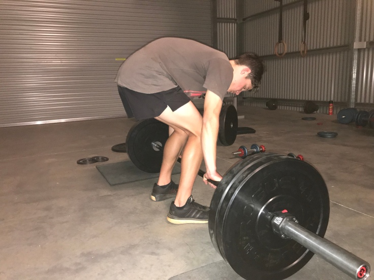 Incorrect deadlift form. Back rounded, looking down.